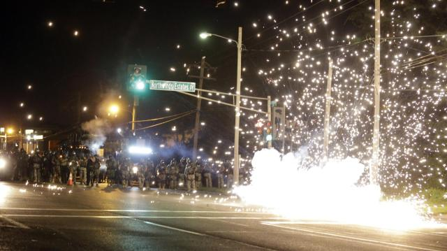 Armed riot cops set off an incendiary device in Ferguson, MO Credit: AP Images